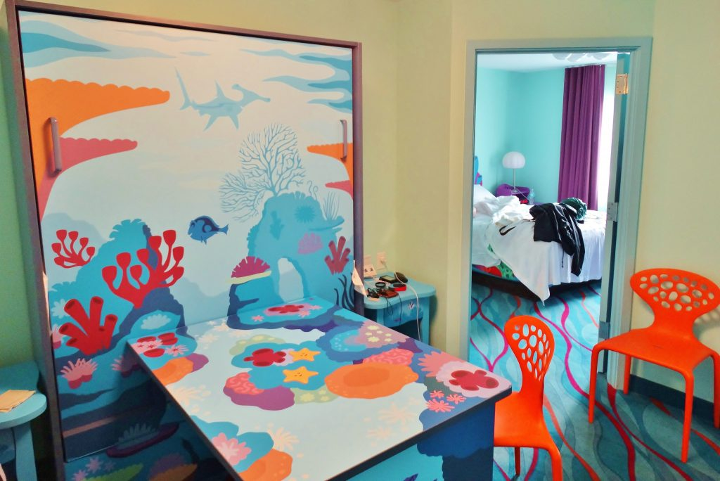 The interior of the Nemo suites at Art of Animation. This table folds downward to turn into another bed. There's also two other beds, and two bathrooms.